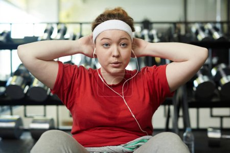 Photo for Portrait of young obese woman doing sit up exercises while working out in gym, breathing heavily with effort and listening to music in headphones - Royalty Free Image