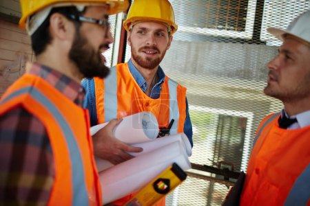 Photo pour Groupe de trois ouvriers portant casques et gilets debout dans la cage d'ascenseur sur chantier de discuter des progrès du développement, exploitation des outils et des plans - image libre de droit