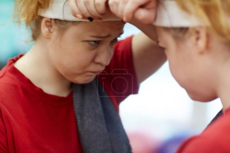 overweight woman looking in mirror
