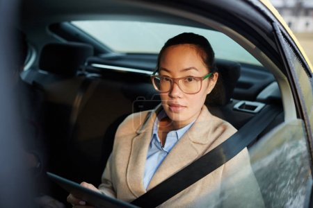 Female broker with gadget looking at camera through cab window