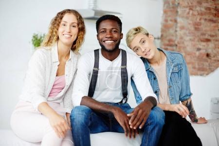 Photo pour Heureuse jeunes filles et des gars afro-américain assis sur le canapé - image libre de droit