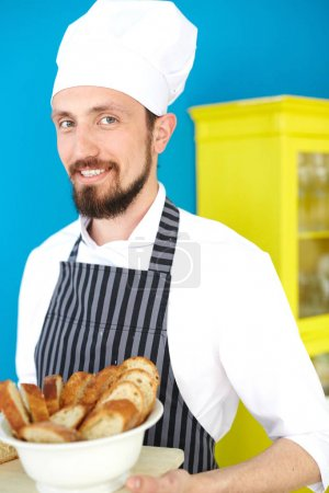 Smiling baker holding plate with sliced bread