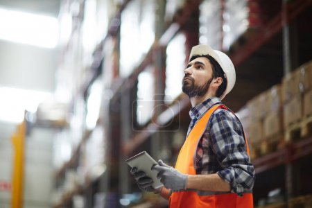 Worker with touchpad revising goods in storehouse