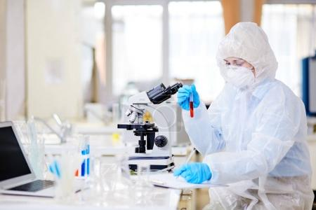 Female microbiologist in hazmat suit writing down results of conducted experiment on clipboard while focused on work at modern laboratory