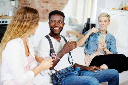 Photo pour Jeune homme et deux jeunes filles avec des boissons après avoir parler à loisir - image libre de droit