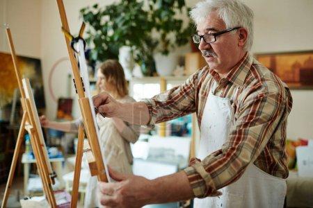 Senior art-class learner studying in modern studio