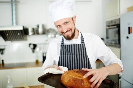 Happy baker taking hot bread from tray