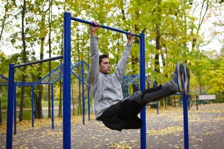 Portrait of handsome young athlete doing leg lifts while hanging on horizontal bar in autumn street workout park