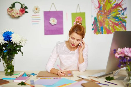 Concentrated female illustrator making sketch with pink pencil while having small talk with her friend on smartphone, messy table with stationery and notebooks on foreground
