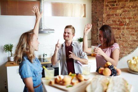 Photo pour Jeunes amis dansants avec boissons ayant parti dans la cuisine - image libre de droit