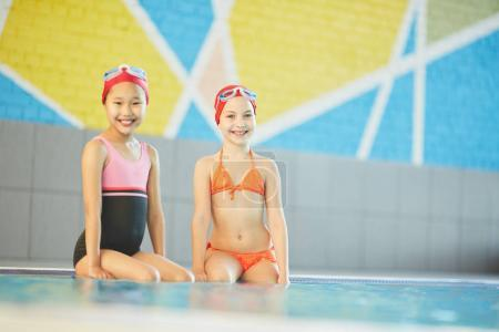 Adorable schoolgirls in swimsuits and swim-caps looking at camer awhile sitting by swimming-pool with their legs in water