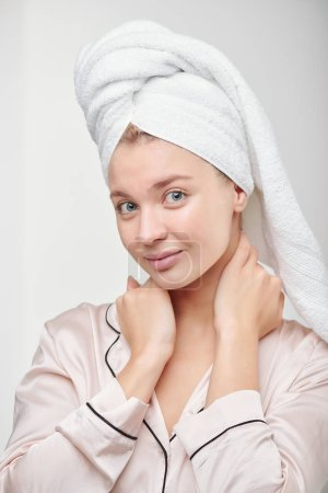 Photo pour Pretty clean girl in silk pajamas going to take care of her face and body after morning shower and washing hair - image libre de droit