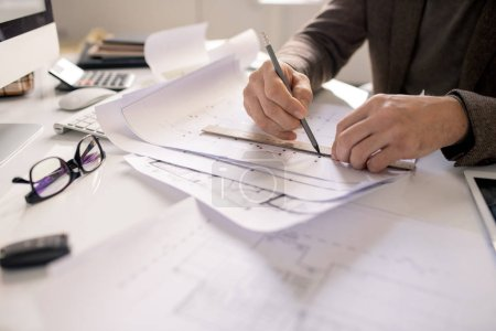 Hands of architect with pencil and ruler drawing line while working over sketch of new building project by workplace