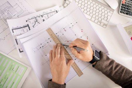 Photo pour Vue d'ensemble des mains de l'ingénieur ou de l'architecte avec ligne de dessin au crayon et à la règle tout en travaillant sur croquis par bureau - image libre de droit