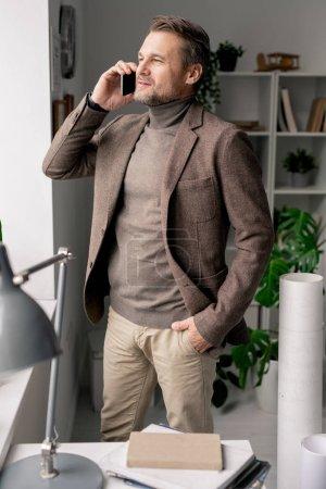Photo pour Architecte mature confiant avec smartphone debout près de la fenêtre du bureau tout en consultant un collègue ou un client - image libre de droit
