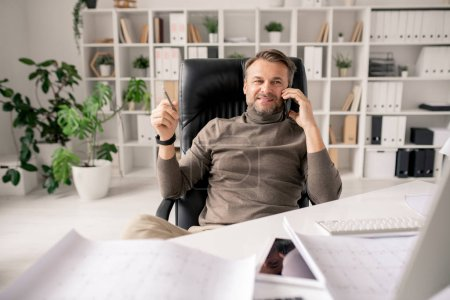 Photo for Cheerful mature architect or businessman with smartphone talking to one of clients or colleague while sitting in office - Royalty Free Image