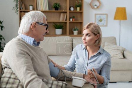 Photo pour Jeune fille blonde prudente avec tonomètre regardant son père aîné tout en mesurant sa tension artérielle à la maison - image libre de droit
