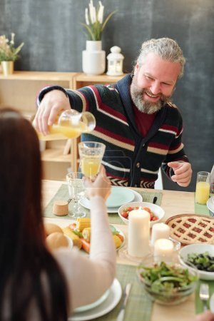Photo for Happy bearded mature man pouring orange juice into glass of his daughter by served festive table over snacks - Royalty Free Image