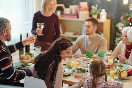 Photo pour Jeune mère et sa petite fille mignonne assis près de l'autre par table servie pendant le dîner de famille le soir de Noël - image libre de droit