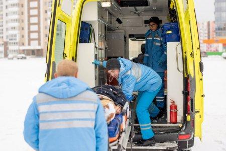 Photo for Paramedics in blue workwear getting stretcher with fixed unconscious man into ambulance car before going to hospital - Royalty Free Image