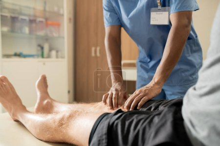 Photo pour Hands of young mixed-race clinician in blue uniform massaging one of legs of patient in hospital - image libre de droit