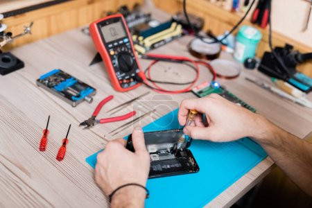 Photo for Hands of gadget repair service master using screwdriver while fixing tiny details of demounted smartphone - Royalty Free Image