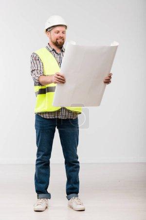 Photo pour Joyeux jeune constructeur barbu en casque blanc, jeans, chemise à carreaux et gilet jaune regardant le plan devant la caméra - image libre de droit