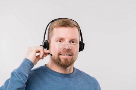 Photo pour Bonne jeune opérateur occasionnel avec casque d'écoute consultant des clients en ligne tout en regardant la caméra en isolement - image libre de droit