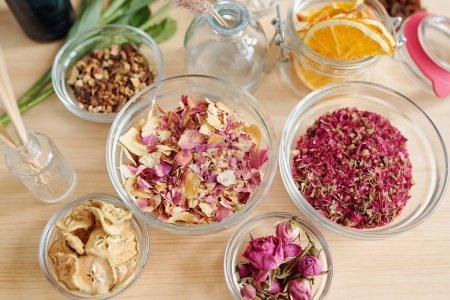 Photo pour Vue du dessus de bols en verre avec pétales de roses, boutons de roses et tranches de poire et d'orange sur une table en bois préparée pour la fabrication du savon - image libre de droit