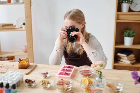 Photo for Young woman with photocamera photographing handmade soap and ingredients on table in studio - Royalty Free Image