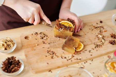 Photo for Hands of female with knife cutting large handmade soap bar with cinnamon, anise and orange slices on wooden board - Royalty Free Image