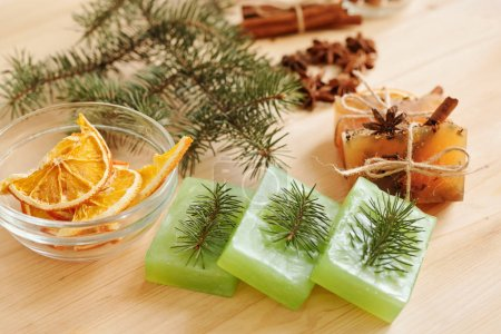 Photo for Composition of handmade soap bars with conifer and aromatic spices and orange slices in bowl that can be used as background - Royalty Free Image