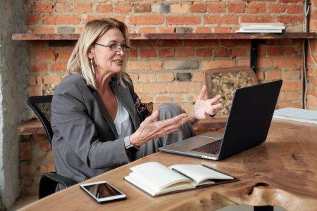 Photo pour Contenu mature dame inspiré avec ses propres ides présenter son plan tout en visioconférence avec partenaire d'affaires en utilisant un ordinateur portable - image libre de droit