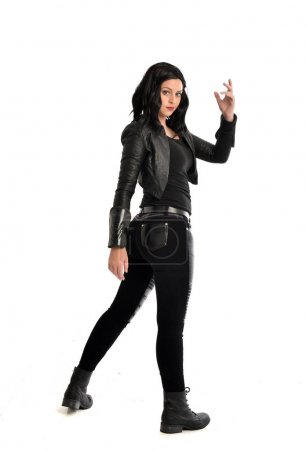 full length portrait of black haired girl wearing leather outfit. standing pose on a white background.