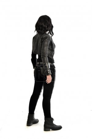 full length portrait of black haired girl wearing leather outfit, facing away from the camera. standing pose on a white studio background.