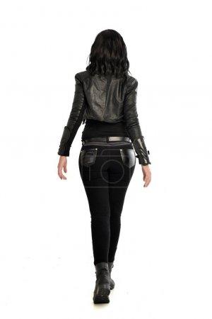 Photo pour Portrait de toute la longueur de la fille aux cheveux noire portant le costume de cuir, à l'opposé de la caméra. posture debout sur un fond de studio blanc. - image libre de droit