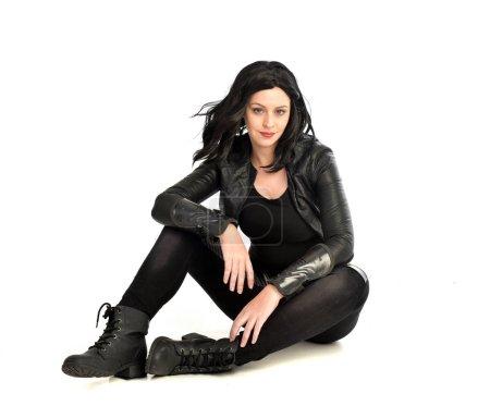 Foto de Retrato de longitud completa de chica de pelo negro con traje de cuero. sentado en la pose, aislado sobre un fondo blanco de estudio . - Imagen libre de derechos