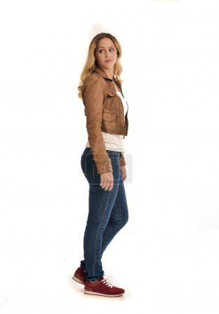 Photo for Full length portrait of blonde girl wearing brown jacket and jeans. standing pose on white background. - Royalty Free Image