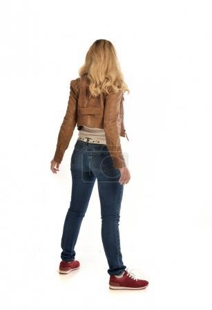 Photo pour Portrait de toute la longueur de la jeune fille blonde portant jeans et veste marron. posture debout sur fond blanc. - image libre de droit