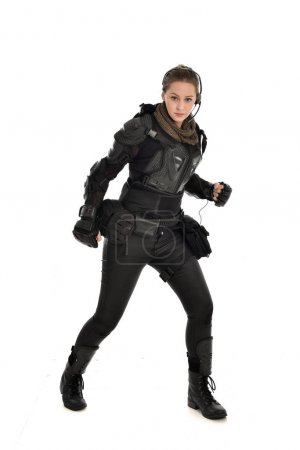 full length portrait of female  soldier wearing black  tactical armour, isolated on white studio background.