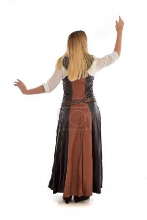 Photo pour Portrait de toute la longueur de la jeune fille blonde portant le costume de fantaisie en cuir marron, pose debout avec le dos à la caméra. isolé sur fond blanc studio. - image libre de droit