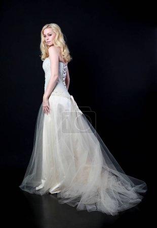 full length portrait of model wearing white bridal ball gown, standing pose on black background.