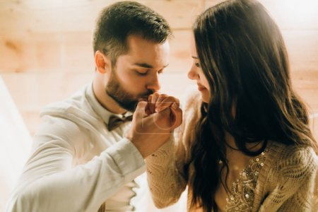 young beautiful couple of newlyweds. Groom kissing bride's hand