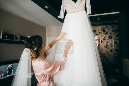 young  beautiful  bride looking at her wedding dress