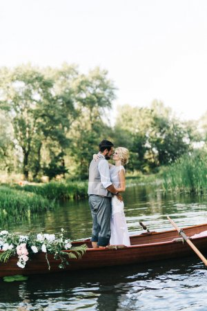 young wedding couple embracing in  in boat