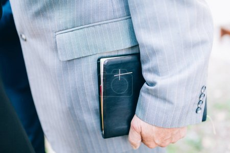 Priest Holding A Bible, close up