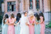 tender bride with smiling bridesmaids dressed in long elegant dresses