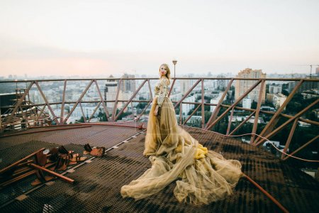 Elegant woman  wearing golden  dress and posing  on the roof