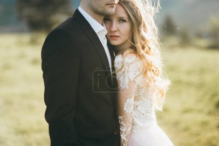 young couple of newlyweds embracing outdoors