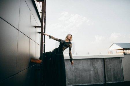 Attractive blonde in black dress posing on  ladder